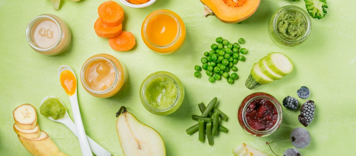 Colorful baby food purees in glass jars with ingredients. Healthy organic baby food concept. Starting solid food, delivery