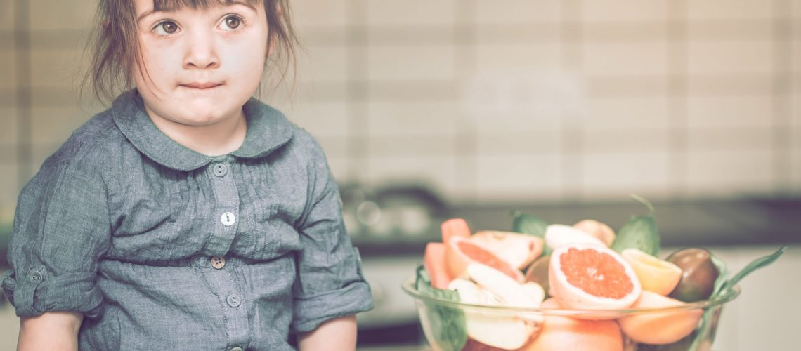 little cute thoughtful girl sitting near a plate with fruit on a kitchen table, concept of a healthy baby food
