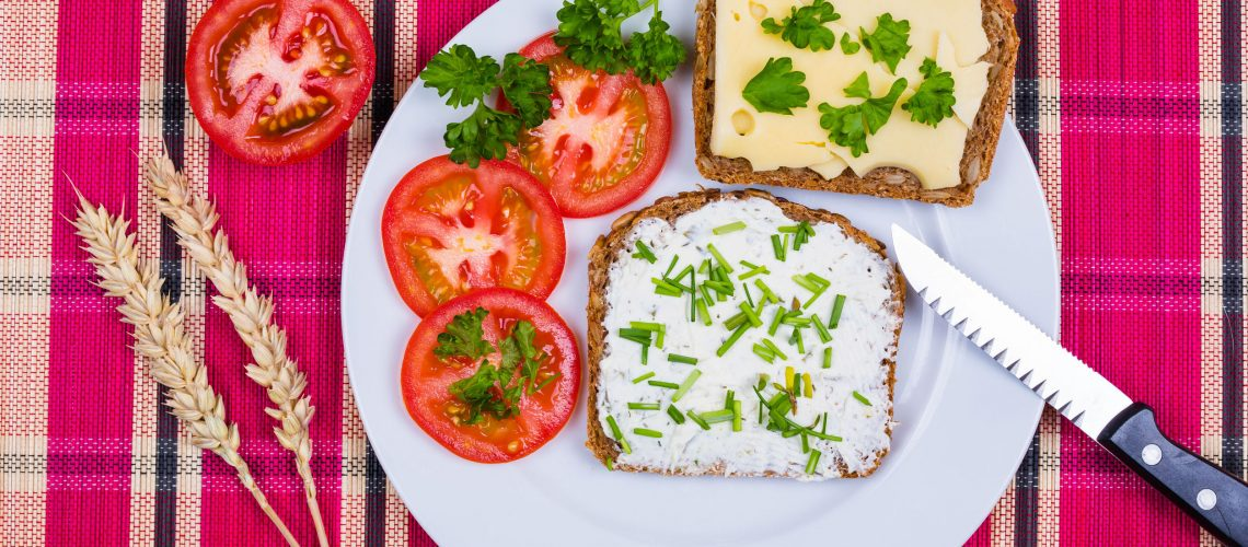 vesper bread on plate with cheese and tomatoes decorated with chives